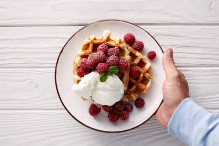 cropped shot of man holding plate of belgian waffles with raspberries and ice cream over white wooden table