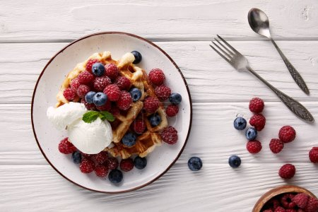 top view of delicious belgian waffles with berries and ice cream on white wooden table