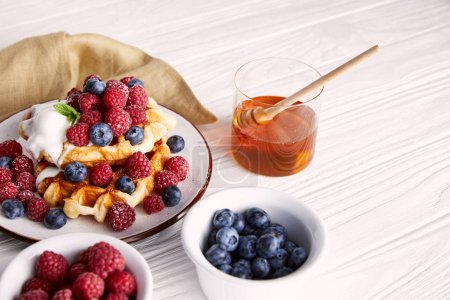 delicious belgian waffles with berries and honey on white wooden table