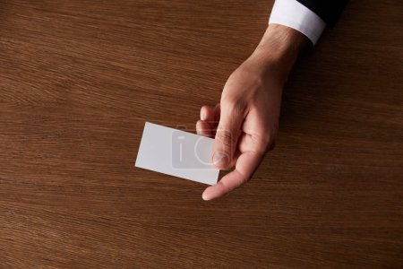 cropped image of businessman giving blank business card at wooden table