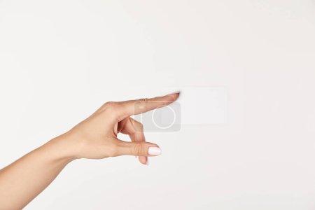 Photo pour Vue partielle d'une femme d'affaires montrant une carte de visite vierge isolée sur fond blanc - image libre de droit
