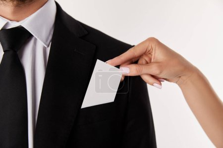 cropped image of businesswoman putting empty visit card in pocket of businessman isolated on white background
