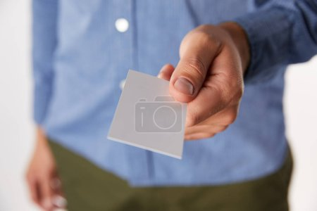cropped image of businessman giving empty business card on blurred background
