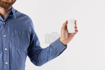 partial view of businessman showing blank visit card isolated on white background
