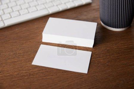 selective focus of stack of empty business cards at table with computer keyboard