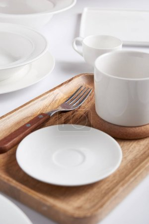 selective focus of wooden tray, fork, various plates, cup and bowl on white table