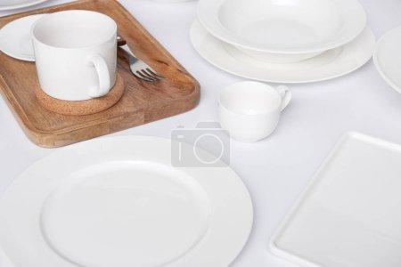 close up view of wooden tray, fork with various plates and cup with bowl on white table