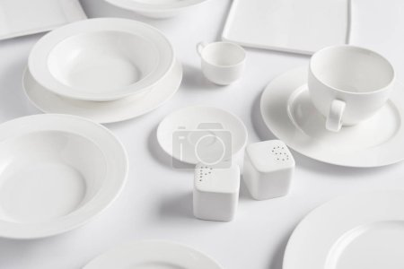 close up view of different plates, cup, bowl, saltcellar and pepper caster on white table
