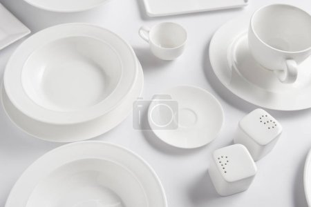 high angle view of different plates, cup, bowl, saltcellar and pepper caster on white table