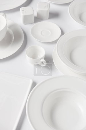 high angle view of different plates, cups, saltcellar and pepper caster on white table