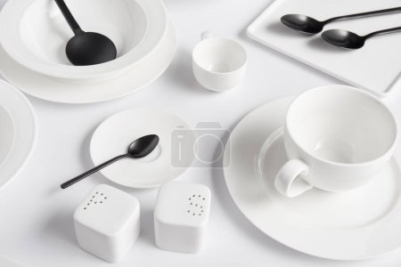 close up view of saltcellar, pepper caster, salad spoon, spoons, bowl, cup and various plates on white table