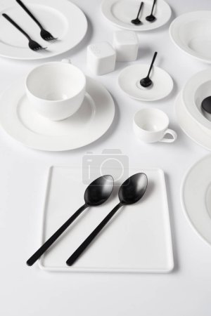 selective focus of different plates, cup, bowl, salt pot and pepper caster, forks with spoons on white table
