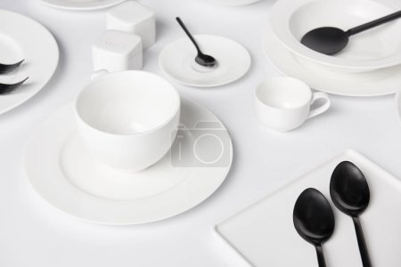 Photo for Selective focus of different plates, cup, bowl, salad spoon, saltcellar and pepper caster, forks with spoons on white table - Royalty Free Image