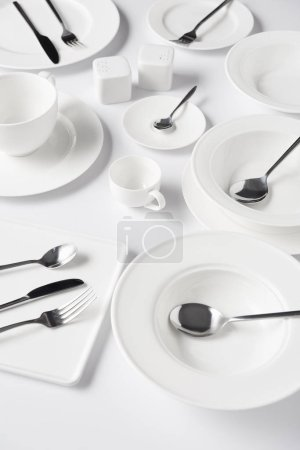 selective focus of different plates, cup, bowl, salt pot and pepper caster, knives, forks with spoons on white table