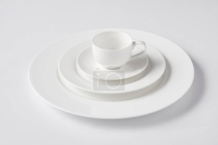 Photo for Selective focus of cup on stack of different plates on white table - Royalty Free Image