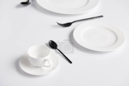 selective focus of cup, spoons, fork and various plates on white table