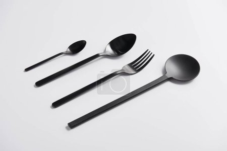 Photo for Close up image of arranged salad spoon, fork and spoons on white table - Royalty Free Image