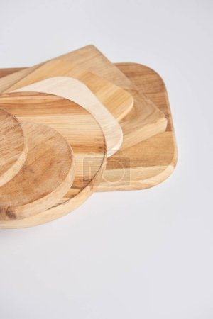 close up shot of stack of different wooden cutting boards on white table