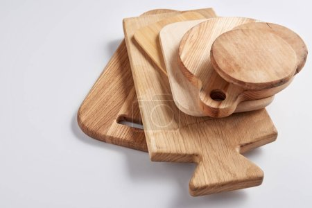 close up image of stack of different wooden cutting boards on white table