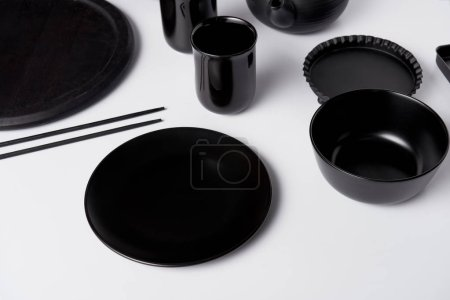 selective focus of black plate, bowl, cups, chopsticks, baking dish and tray on white table