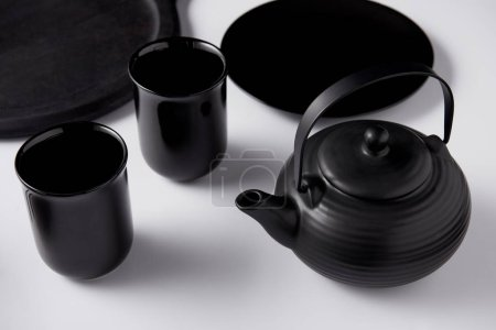 selective focus of black teapot, cups, plate and tray on white table