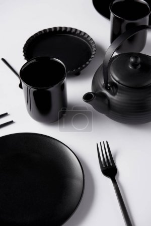 Photo for Close up view of black teapot, plate, cups, fork, chopsticks and baking dish on white table - Royalty Free Image