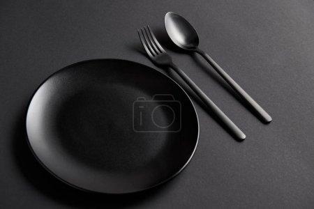 Photo pour Vue grand angle de cuillère noire, fourchette et plaque sur table noire, concept minimaliste - image libre de droit
