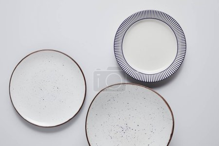 top view of three different ceramic plates on white table, minimalistic concept
