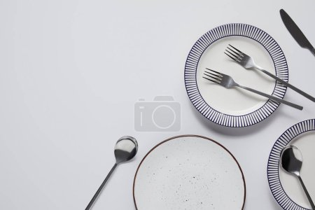 top view of different ceramic plates, forks, spoons and knife on white table