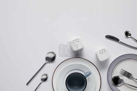 top view of saltcellar, pepper caster, spoons, knife, fork, cup and plates on white table