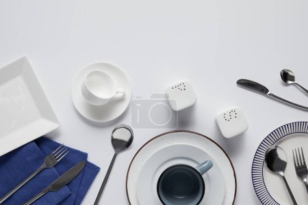 top view of various ceramic plates, saltcellar, pepper caster, cup, kitchen towel, forks, spoons and knives on white table