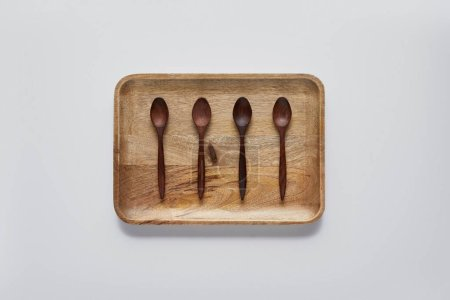 top view of wooden tray with wooden spoons on white table, minimalistic concept