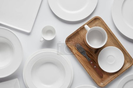 top view of cup, different plates, wooden tray, bowl and fork on white table