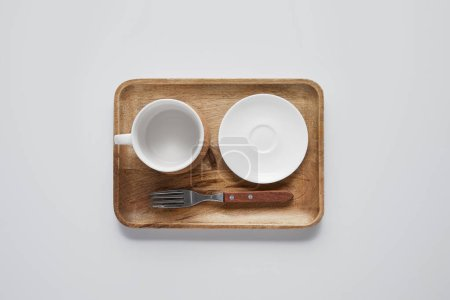 top view of wooden tray with plate, bowl and fork on white table, minimalistic concept