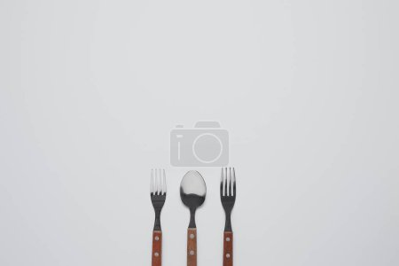 top view of spoon between forks on white table, minimalistic concept