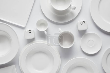 top view of various plates, bowl, saltcellar, pepper caster and cups on white table