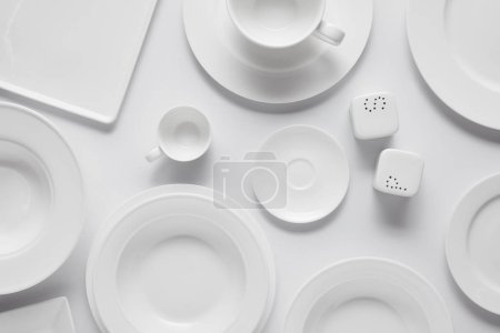 top view of different plates, bowl, saltcellar, pepper caster and cup on white table