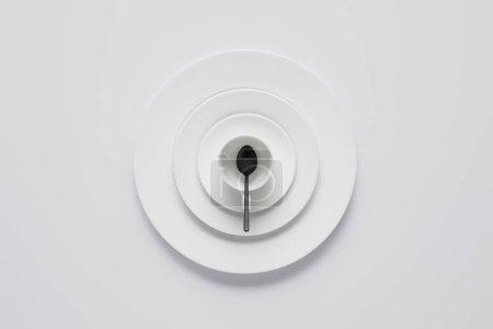 Photo pour Vue de dessus de la pile disposée de diverses assiettes, tasse et cuillère sur la table blanche - image libre de droit