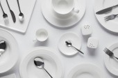 top view of spoons, forks, knives, different plates, bowl, saltcellar, pepper caster and cup on white table