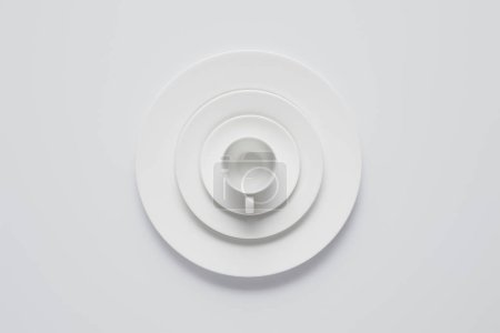 top view of arranged stack of different plates and cup on white table, minimalistic concept