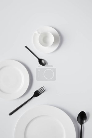 Photo for Top view of plates, cup, fork and black spoons on white table - Royalty Free Image