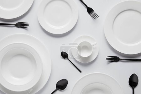 top view of various plates, cup, black spoons and forks on white table