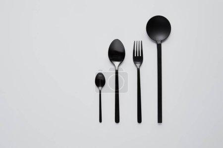 Photo pour Vue de dessus de différentes cuillères noires, fourchette et cuillère à salade sur table blanche, concept minimaliste - image libre de droit