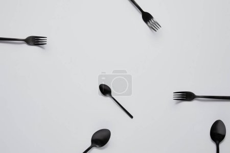 top view of various black spoons and forks on white table