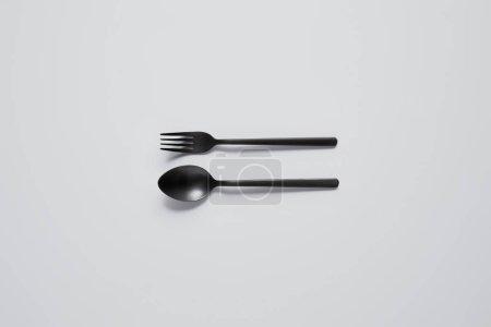 Photo pour Vue de dessus de cuillère noire et fourchette sur table blanche, concept minimaliste - image libre de droit