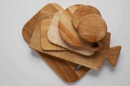 top view of stack of different wooden cutting boards on white table