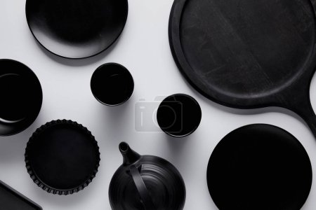 top view of black teapot, plates, bowl, baking dish and cups near tray on white table
