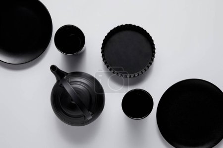 top view of black teapot, plates, baking dish and cups on white table