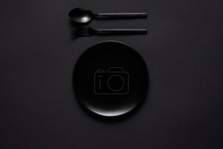 top view of black plate, fork and spoon on black table, minimalistic concept