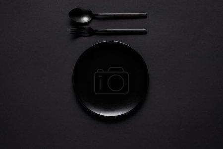 Photo pour Vue de dessus de la plaque noire, fourchette et cuillère sur table noire, concept minimaliste - image libre de droit